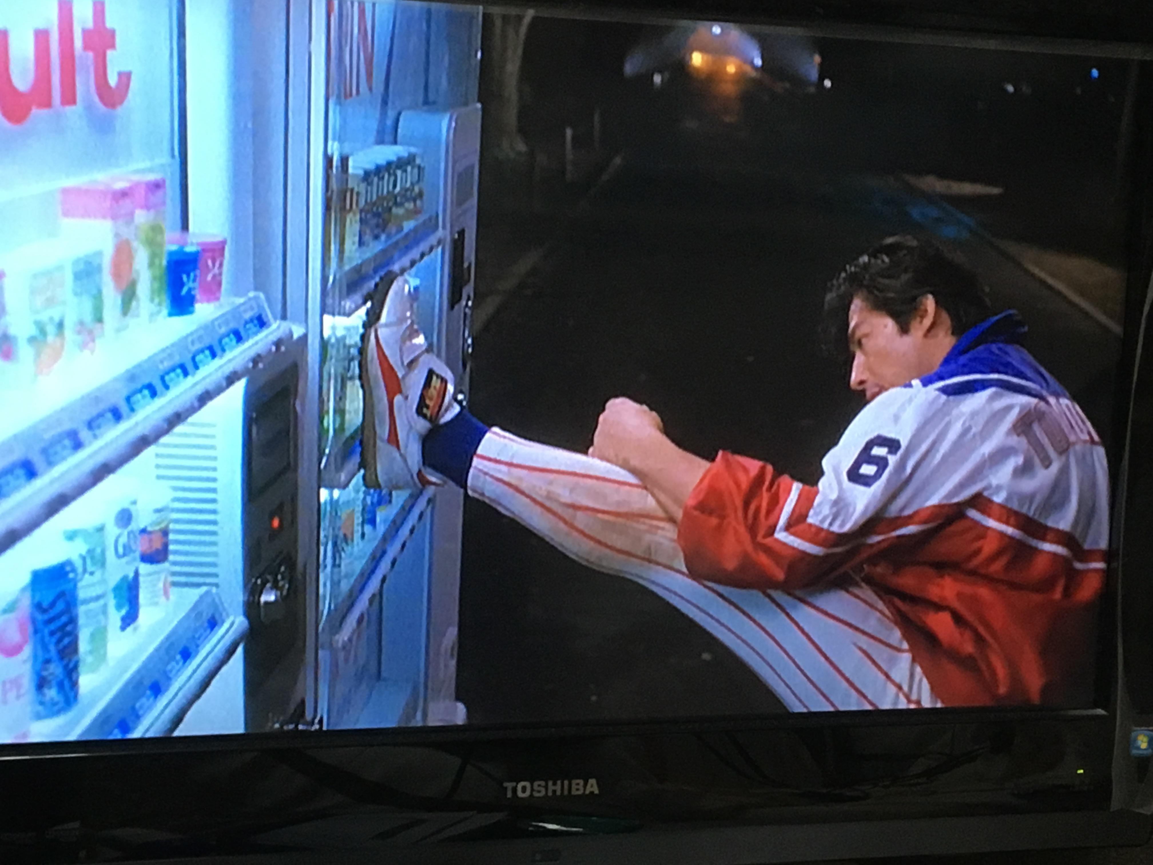 自動販売機に八つ当たりする真田広之。